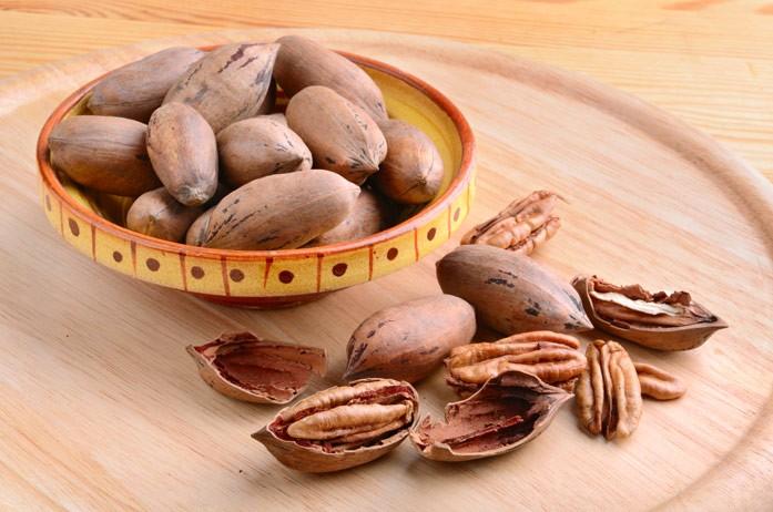 фото ореха пекан с треснувшей скорлупой в этнической миске