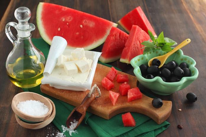 свежий арбуз, оливки, сыр и арбузное масло на столе