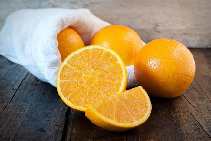 цельные и разрезанные апельсины высыпались из тканевого мешочка