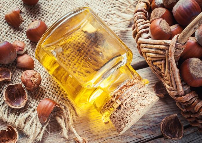 Бутылка с маслом фундука и орехи в корзине