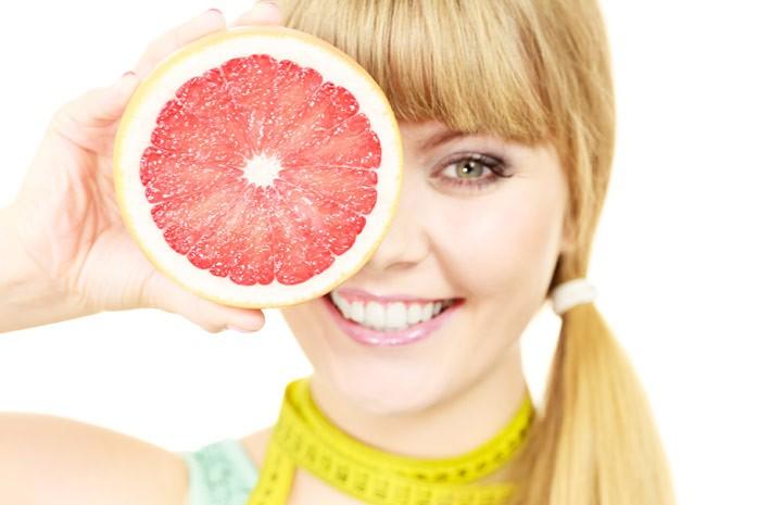 девушка держит половинку грейпфрута