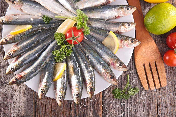 Красиво разложенная на тарелке рыбка хамса с приправами