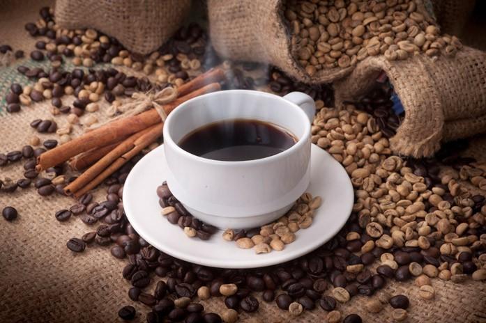 Мешки с кофейными зёрнами и чашка с напитком