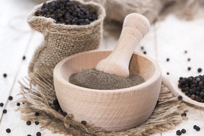 Мешочек с натуральным чёрным перцем горошком и миска с молотым