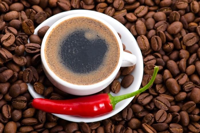 Чашка с черным кофе и острый перец чили на рассыпанных зёрнах