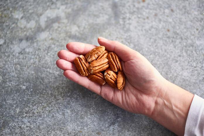 орехи карии иллинойской в женской ладони