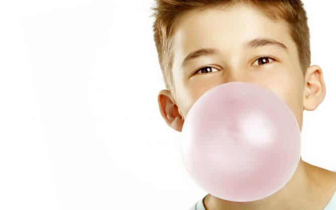 мальчик надувает пузырь из жвачки